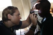 Above, Karin Feltman, a Lawrence Memorial Hospital nurse, performs an eye exam on a boy while serving in Haiti on a 10-day mission trip, one year after a devastating earthquake rocked the country.
