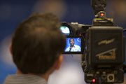 Kansas University football coach Turner Gill is seen in a camera man's monitor during a news conference. Gill was announcing his recruiting class of 2011 on Wednesday, Feb. 2, 2011 at Mrkonic Auditorium.