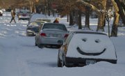 A smiley face greets Lawrence residents on a car parked in the street Wednesday, Feb. 2, 2011. A blizzard hit the city dropping at least 8 inches of snow on Tuesday.