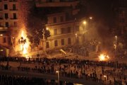 Pro-government demonstrators, bottom, clash with anti-government demonstrators, top right, as a palm tree burns from a firebomb, in Tahrir Square, the center of anti-government demonstrations, in Cairo, Egypt, early today. Thousands of supporters and opponents of Egyptian President Hosni Mubarak battled in Cairo's main square all day Wednesday, raining stones, bottles and firebombs on each other in scenes of uncontrolled violence as soldiers stood by without intervening.