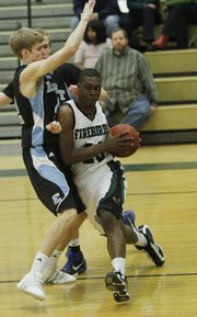 Free State's Eric Watson drives against Shawnee Missions East's Sean Camerons on Friday, February 4, 2011 at FSHS.