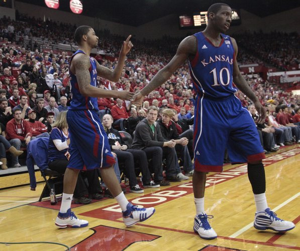 Kansas forward Marcus Morris, left, shakes hands with Tyshawn Taylor, right, and points to teammate Brady Morningstar after Morris was fouled during the second half Saturday, Feb. 5, 2011 at the Devaney Center in Lincoln, Neb.