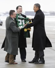 President Barack Obama receives an autographed Green Bay Packers Charles Woodson jersey from Wisconsin Gov. Scott Walker, center, and Green Bay Mayor Jim Schmitt upon his arrival Jan. 26 in Green Bay, Wis.