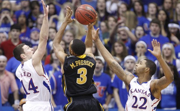 Kansas defenders Tyrel Reed and Marcus Morris defend a shot by Missouri guard Matt Pressey during the second half on Monday, Feb. 7, 2011 at Allen Fieldhouse.