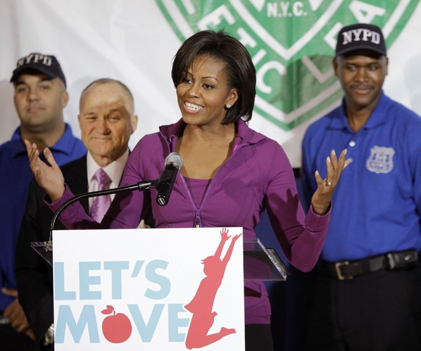 "In this Nov. 18, 2010, file photo, first lady Michelle Obama, center, is joined by New York City Police Chief Raymond Kelly, second from left, as she speaks to children while promoting her ""Let's Move!"" exercise initiative at the Police Athletic League Harlem Center in New York."