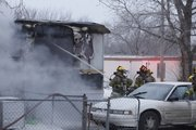 Lawrence fire crews battle a structure fire in the Gaslight Village on Tuesday. Six people were displaced from the home.
