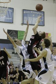 Lawrence High's Logan Henrichs (32) goes over the Shawnee Mission East defense Tuesday, Feb. 8, 2011.