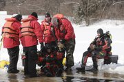 Diver Adam Heffley, left, is helped out of a frozen pond by members of the Douglas County Underwater Search and Rescue team.  Diver Earl Barnes, right, gets ready to take his turn in the water. Barnes is the most experienced diver on the team. 