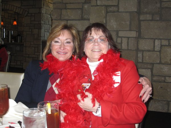 Kathy Clausing Willis, vice president of Lawrence Memorial Hospital, and Janice Early, communication director at LMH, sport the red boas they received for giving a donation to the American Heart Association. They attended the Go Red For Women luncheon on Friday, Feb. 11, 2011.