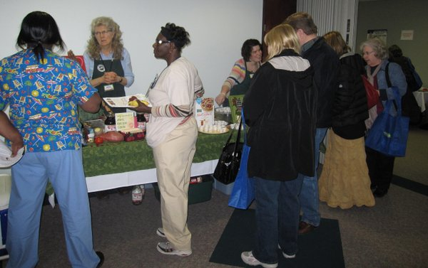 Behind the booth, Nancy O'Connor, left, and Lily Siebert, both of The Merc, answer questions about nutrition during the Health Hearts Fair on Feb. 12, 2011, at Lawrence Memorial Hospital.
