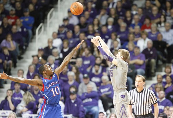 Kansas State guard Will Spradling puts up a three-pointer over Kansas guard Tyshawn Taylor during the second half on Monday, Feb. 14, 2011 at Bramlage Coliseum.