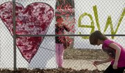 "Adeline Unekis, center, a third-grader at Pinckney School, attaches ribbons to the fence in front of Pinckney while classmate Evelyne Heironimus-Bishop, right, chases down a wind-blown ribbon Monday. Youngsters wrote on the ribbons what they loved about their school and attached them next to the ""We Love Pinckney"" banners in front of the school building at 810 W. Sixth St."