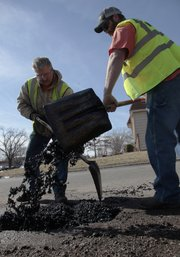 City employees John Barnes, Pamona, left, and Andy Breedlove, Baldwin City, patch up a pothole Monday, Feb. 14, 2011 near the intersection of Ridge Court and 27th Street.