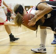 Lawrence High senior Rachel Kelly tumbles over Olathe Northwest sophomore Jaylah Jackson's back as the two battle for a rebound during Lawrence High's game against Olathe Northwest on Friday, Feb. 18, 2011 in Lawrence. Olathe Northwest won the game, 63-47.