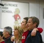 Garrett Wagner, center, is joined by his parents Maggie, left, and Bill as they sing the Lawrence High alma mater during Senior Night festivities Friday, Feb. 18, 2011 at Lawrence High.