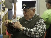 Tom Smith, of Springfield, Mo., checks off his list of train parts as he dressed the part of a train conductor.