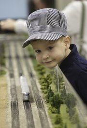 Wearing an engineer hat, Stefen Halm, 5, of Belton, Mo., gets an eyeful of a model train passing Saturday at the Douglas County Fairgrounds. Model train enthusiasts packed into Building 21 for the 10th Annual Lawrence Model Railroad Club Train Show.