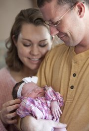 Patrick and Crystal Leming are pictured with their infant daughter, Alyssa, in their Lecompton home on Monday. Alyssa was born before her mother could make it to the delivery room at Lawrence Memorial Hospital, and arrived in the elevator.