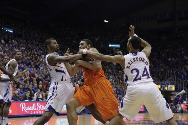 Marcus Morris (left) and Travis Releford tangle with Oklahoma State's Marshall Moses during the first half Monday, Feb. 21, 2011 at Allen Fieldhouse.