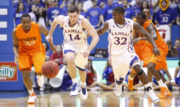 Kansas guard Tyrel Reed (14) chases down a loose ball with teammate Josh Selby and Oklahoma State guard Roger Franklin (32) during the first half on Monday, Feb. 21, 2011 at Allen Fieldhouse.