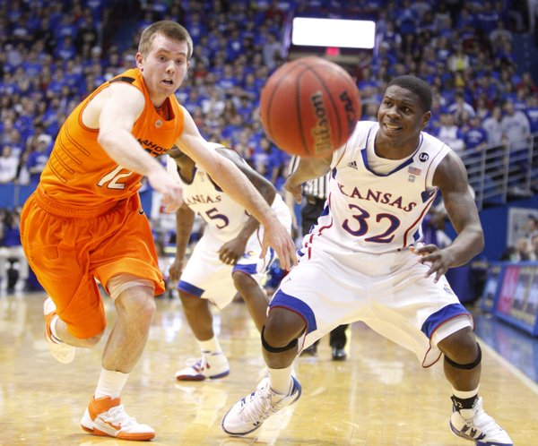 Oklahoma State guard Keiton Page knocks the ball away from Kansas guard Josh Selby during the first half on Monday, Feb. 21, 2011 at Allen Fieldhouse.