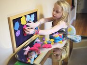 Tabitha Metts, 5, daughter of Christian and Ann Metts, Lawrence, tries out a felt board created by Katie Kritikos. This is an easy and cheap project to put together before spring break.