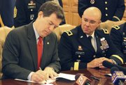 Kansas Gov. Sam Brownback signs an executive order extending a military affairs council that advises him on matters relating to the state's military installations and the Kansas National Guard, Thursday, Feb. 24, 2011, at the Statehouse in Topeka, Kan. Watching him is Maj. Gen. Lee Tafanelli, state adjutant general.