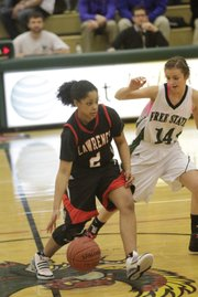 Lawrence High senior Brittany Ray works drives around Free State's Lynn Robinson on Friday, February 25, 2011 at Free State.
