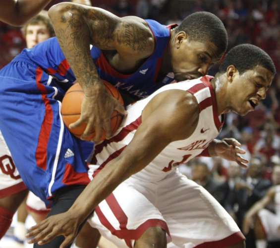 Kansas forward Thomas Robinson regains his footing as he lands on the back of Oklahoma guard Carl Blair Jr. during the first half on Saturday, Feb. 26, 2011 at the Lloyd Noble Center in Norman, Okla.