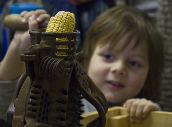 Chauncey Willesen, 4, tries his hand at corn shelling Saturday at the second Kaw Valley Seed Fair at the Douglas County Fairgrounds.