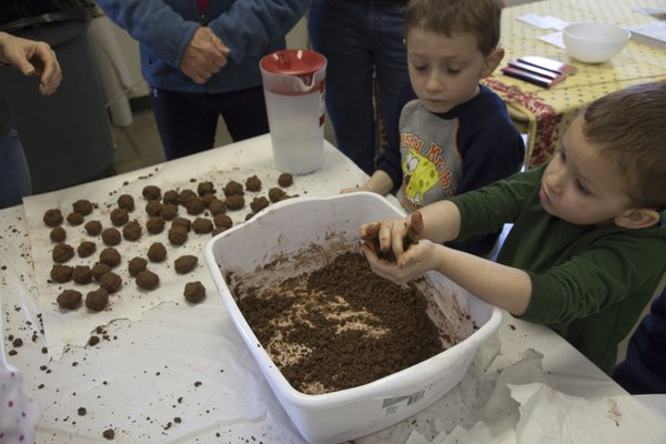 Brothers Ryan Beach, 6, and Noah Beach, 4, McLouth, tried their hands at making some seed bombs at the second annual Kaw Valley Seed Fair Saturday, Feb. 26,2011, at the Douglas County Fairgrounds.