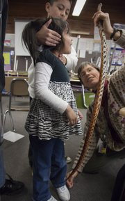 Anna Busby, a sixth-grade teacher at Schwegler School, stretches out a corn snake to show how long it is compared to  the height of  kindergartner Kimberly Cantu.