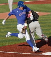 Kansas runner Zac Elgie runs safely to first base after the ball bounces off the Southern Utah first baseman's glove in the fifth inning of the first game of a double-header Tuesday, March 1, 2011 at KU's Hoglund Ballpark.