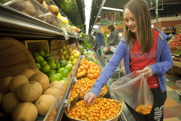 Madison Vaughn, 12, picks out some kumquats Wednesday, March 2, 2011, at the Community Mercantile while shopping for groceries with her mother.