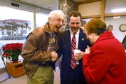 Sheahon Zenger, athletic director for Kansas University, center, shares a laugh with hometown friends Ed Stehno, Hays, left, and Stehno's wife, Donna, during a gathering on Wednesday at Augustine's Bakery in Hays.