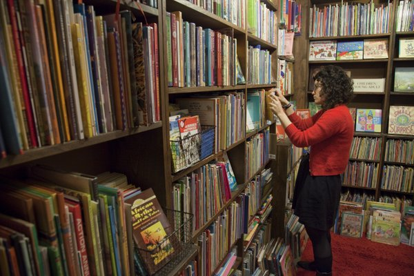 Anna Luna, clerk at The Dusty Bookshelf, 708 Mass., sorts through the children's section of the store. The bookstore was voted best bookstore in the 2011 Best of Lawrence competition.