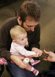 Brian Vancil holds his 8-month-old daughter, Tessa, as she pets a toad at Prairie Park Nature Center. They were attending a February outing of the Daddy and Me Playgroup.