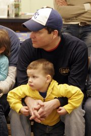 Justin Hoffman holds his 3-year-old son, Caden, as they  listen to a story at Prairie Park Nature Center. Hoffman, a first-time visitor to the Daddy and Me playgroup, said he was seeking other dads to talk to about their experiences.