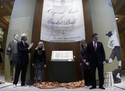 "Julian Zugazagoitia, left, director of the Nelson-Atkins Museum of Art; Sarah Rowland; Suzanne Deal Booth; and David Booth, from left, smile after the unveiling of James Naismith&squot;s original rule of ""Basket Ball"" at the museum Friday, March 4, 2011, in Kansas City, Mo. The Booth family purchased the Rules of Basket Ball at a Sotheby&squot;s auction for more than $4 million; it will be displayed at the museum and will eventually be moved to the Kansas University in Lawrence."