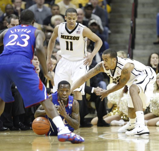 Kansas guard Tyshawn Taylor pushes the ball to forward Mario Little as he is pressured by Missouri defenders Laurence Bowers and Michael Dixon (11) during the first half on Saturday, March 5, 2011 at Mizzou Arena.