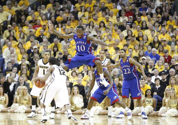 Kansas guard Tyshawn Taylor jumps as he defends drive by Missouri guard Marcus Denmon during the second half on Saturday, March 5, 2011 at Mizzou Arena.