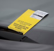 A parking ticket rests under a wiper blade on Massachusetts Street on Monday, March 7, 2011.