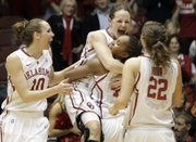 Oklahoma players, from left, Carlee Roethlisberger, Whitney Hand, Jasmine Hartman and Morgan Hook celebrate after defeating Texas Tech. OU won, 71-69, Wednesday in the Big 12 tournament in Kansas City, Mo.