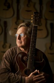 "Jim Baggett, owner of Mass Street Music, is pictured Monday, March 7, 2011, with an early 1900s Gibson Style O Artist guitar. Baggett, who insists his passion is restoring vintage guitars, has become a regular fixture on the PBS series ""Antiques Roadshow."""