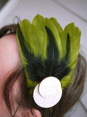 A headband with green feathers lends flair to a St. Patrick's day outfit.