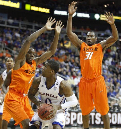 Kansas forward Thomas Robinson gets caught under Oklahoma State defenders Jarred Shaw (1) and Matt Pilgrim (31) during the first half on Thursday, March 10, 2011 at the Sprint Center in Kansas City.