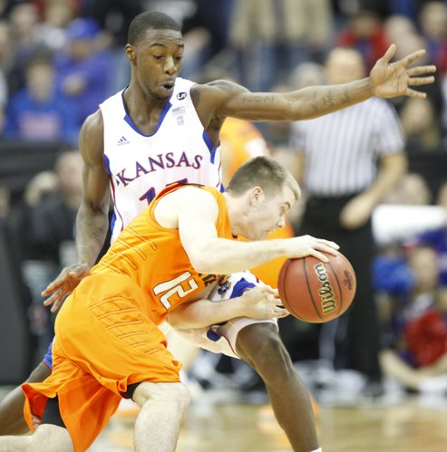 Kansas guard Elijah Johnson defends against a drive by Oklahoma State guard Keiton Page during the first half on Thursday, March 10, 2011 at the Sprint Center in Kansas City.