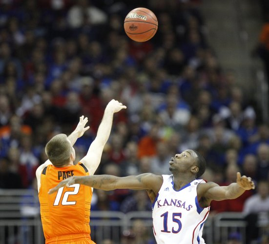 Kansas guard Elijah Johnson watches as Oklahoma State guard Keiton Page puts up a three during the second half on Thursday, March 10, 2011 at the Sprint Center in Kansas City.