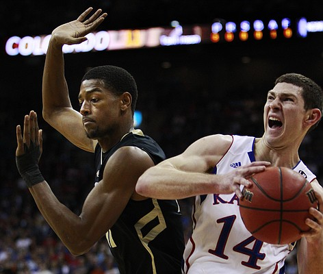 Kansas guard Tyrel Reed (14) is fouled by Colorado guard Cory Higgins, left, during the first half of an NCAA college basketball game in the semifinals of the Big 12 men's basketball tournament in Kansas City, Mo., Friday, March 11, 2011.
