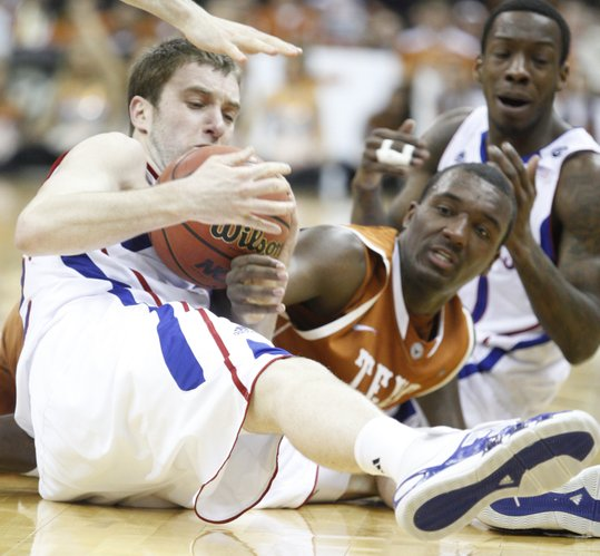 Kansas guard Brady Morningstar wrestles for the ball with Texas forward Jordan Hamilton during the second half on Friday, March 11, 2011 at the Sprint Center. In back is KU guard Tyshawn Taylor.